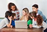 Lehrer und eine Gruppe Schüler am Laptop - 242259509