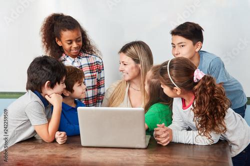 Lehrer und eine Gruppe Schüler am Laptop