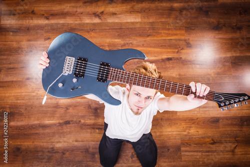 Proud man raising his electric guitar - 242260112