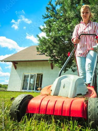 Foto Murales Woman mowing green grass