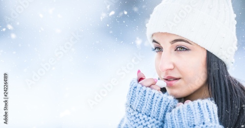 Attractive young woman l protecting lips with lip balm in snowy and frozen weather