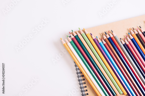 set of wooden colorful pencils on notebook on white background