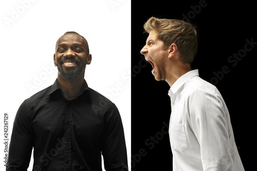 The screaming afro and caucasian men. Mixed couple. Dynamic image of male models on white and black studio. Human facial emotions concept.