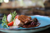 Duck confit with salad , baked apple and raspberry sauce served on wooden table - 242269734