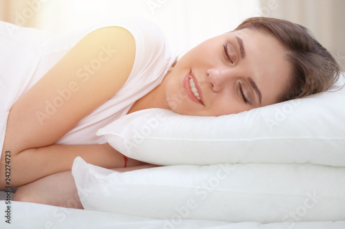 Leinwanddruck Bild Beautiful young and happy woman sleeping while lying in bed comfortably and blissfully smiling