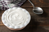 greek yogurt in a ceramic bowl next to a spoon on a brown wooden background - 242275550
