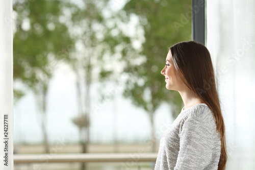 Wall mural Woman looking outside through window at home