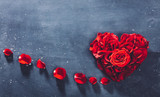 Heart-shaped red roses on stone background. - 242277385
