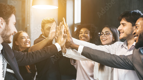 High-five for success. Diverse group of business colleagues in office - 242278759