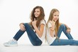 Two teen girl friends sit back to back on isolated white background.