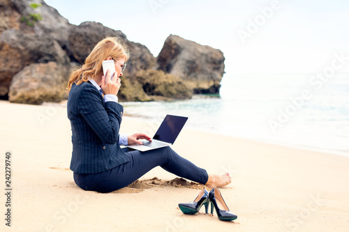 Business woman working on the beach with laptop computer