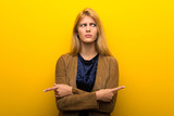 Blonde girl on vibrant yellow background pointing to the laterals having doubts
