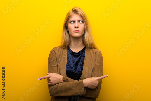 Leinwanddruck Bild Blonde girl on vibrant yellow background pointing to the laterals having doubts