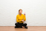Young girl sitting on the floor pointing a great idea and looking up - 242282515