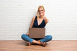 Leinwandbild Motiv Blonde girl sitting on the floor with her laptop giving a thumbs up gesture and smiling on white brick wall background