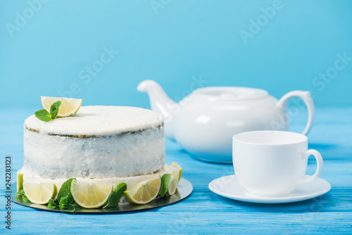 cake decorated with slices of lime near white cup and tea pot isolated on blue