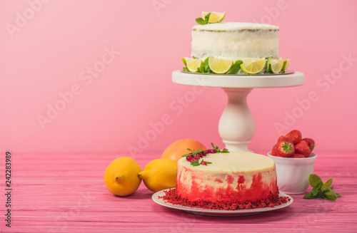 cake decorated with currants and mint leaves near fruits and white cake with lemon slices on pink wooden surface isolated on pink
