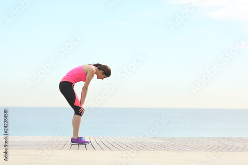 Exhausted runner resting on the beach after exercise