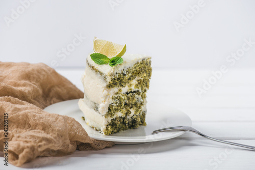 piece of white cake decorated with lime slice and mint leave with fork on saucer isolated on white