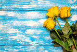 A bouquet of yellow roses lies on a bluewooden background  - 242288926