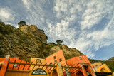 View from below of the cliff on the port of Alassio with coloured, abandoned buildings and cloudy sky, Liguria, Italy