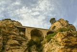 View from below of the cliff on the port of Alassio with the arches supporting the Aurelian Drive, Liguria, Italy