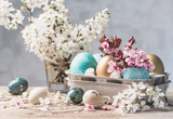Easter eggs and spring flowers on rustic wooden background.Easter holiday card copy space.