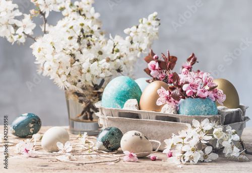 Foto Murales Easter eggs and spring flowers on rustic wooden background.Easter holiday card copy space.