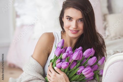 Close up portrait of young beautiful woman indoors. Attractive woman with flowers. Female with tulips. Spring bouquet. - 242296556