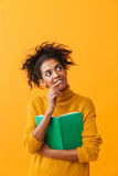 Cheerful african woman wearing sweater holding a book - 242299195