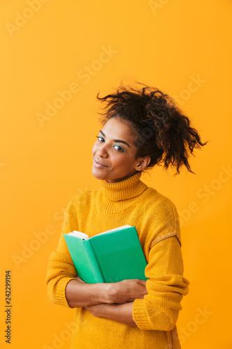 Leinwandbild Motiv Cheerful african woman wearing sweater holding a book