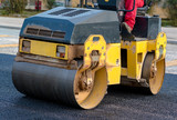 Worker leads the vibrating road roller to compact the asphalt laid out for the construction of a road - 242299732