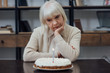 upset senior woman sitting at table, propping chin and looking at birthday cake with burning candle at home