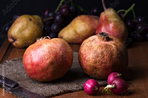 Foto Murales pomegranates and pears with other fruit bodegon with classic light on wood
