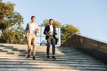 Photo of european businessmen in suits walking outdoor with takeaway coffee, during sunny day