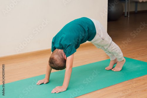Cute little boy is learning to do yoga in the gym - 242304580