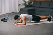 bi-racial athlete doing plank exercise on  fitness mat