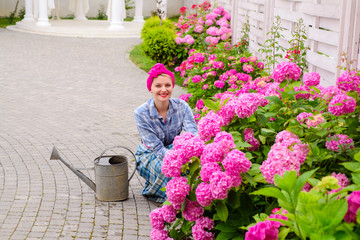 happy woman gardener with flowers. woman care of flowers in garden or greenhouse. gardener is happy for results. gardening is my passion. everything for your gardening needs. soils and fertilizers.