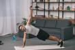 bi-racial man doing plank exercise on fitness mat in living room