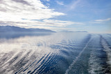 Wake Of Boat On Lake In Alaska Surrounded By Mountains And Forests - 242307349