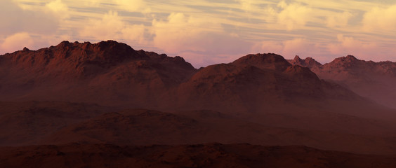 Sandy mountains with cloudy sky at sunset.