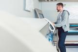 Mann arbeitet am Großformatdrucker in Werbemittelherstellung