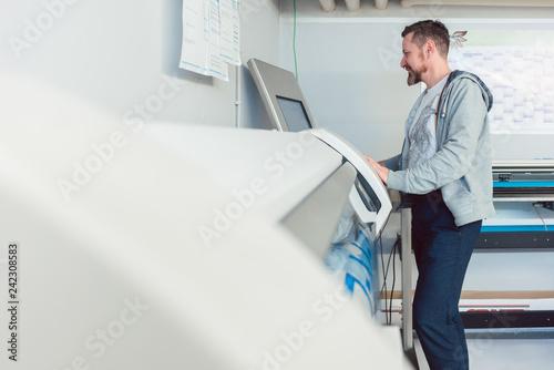 Mann arbeitet am Großformatdrucker in Werbemittelherstellung  - 242308583