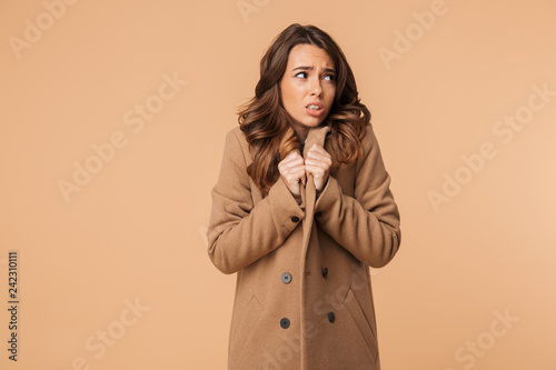 Beautiful frozen emotional woman posing isolated dressed in warm jacket.