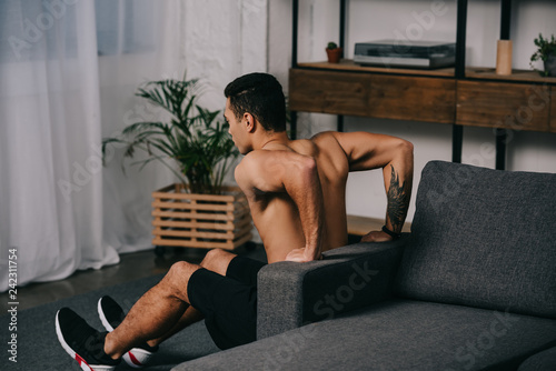 tattooed mixed race man workout  near sofa in living room