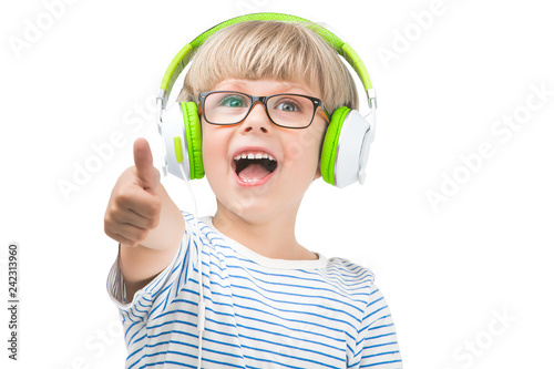 Isolated on white cute child listening to the music on earphones. Boy on white background with headphones. - 242313960