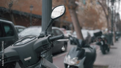 Street view with several scooters parked alongside. Small Christmas ball hanging on one of them