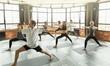 Leinwandbild Motiv Millennials practicing yoga in a modern studio