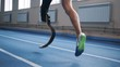 Sportsman with bionic leg jogging on a track, side view.