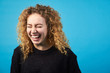 Funny attractive redhead curly girl laughing  with closed eyes on blue background.